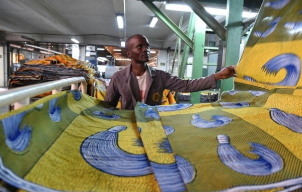 A man checks a piece of cloth in a production line at the Uniwax factory in Abidjan Photo- AFP- Issouf Sanogo